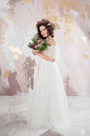 Elegant brunette girl bride with flowers. Beautiful young bride in a lush wedding wreath of fresh flowers. Studio portrait Stock Photo