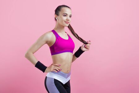 Young athletic attractive girl brunette with a ponytail in a bright tight top straightens her hair, high ponytail, on a pink background. Copy space