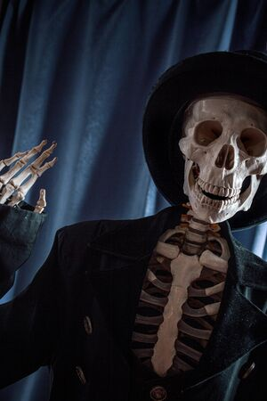 Funny human skeleton in a jacket and bowler hat. Halloween, skeleton waving cheerfully Banque d'images