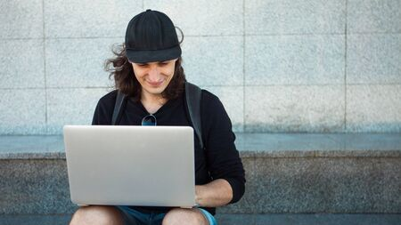 A young brunette man with long hair sits on the granite steps in the shade, with a laptop on his lap and makes a photo on a smartphone. Summer windy day. Copy space. Front view