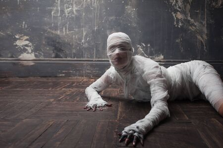 Scary mummy creeps on you. The girl with the bandage Crawling on the floor. Halloween costume Stock Photo