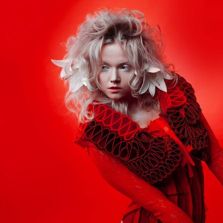 Shades of red. Strange attractive blonde woman, with white eyelashes, in a red outfit, on a red background, with white lily flowers in her hair. Copyspace.