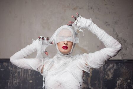 Mummy girl blindfolded. Portrait of a young beautiful woman in bandages all over her body. Halloween or plastic surgery concept Фото со стока