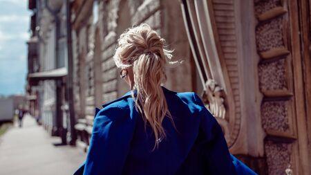 Spazieren Sie durch das historische Zentrum. Ein schönes Mädchen, blond in einer blauen Jacke vor dem Hintergrund grauer historischer Gebäude mit Ornamenten, führt entlang. Jacke über die Schultern geworfen. Ansicht von hinten.