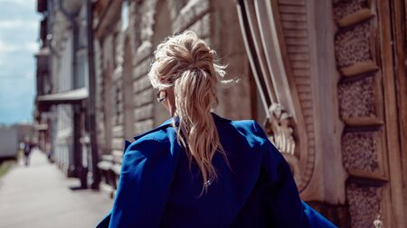 Walk through the historic center. A beautiful girl, blonde in a blue jacket against a background of gray historic buildings with ornaments, leads along. Jacket thrown over shoulders. View from back.