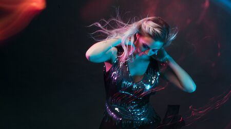 Attractive dancing blonde in the club, neon light, motion effects. Black background, long exposure Stock Photo
