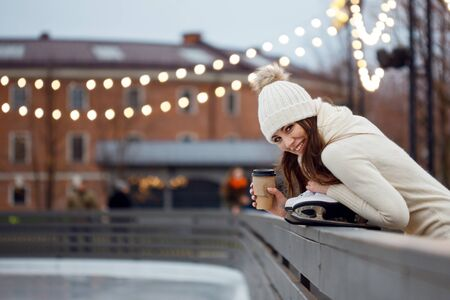 Charming young woman in the Park near the ice rink. Smiling brunette with skates, winter leisure and relaxation Imagens - 131334156