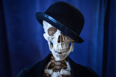 Funny human skeleton in a jacket and bowler hat. Skeleton invites to Halloween.