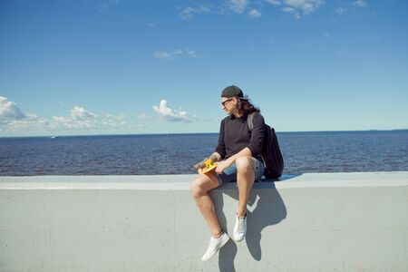 A young man with long hair in a baseball cap, denim shorts, sweatshirt and black glasses is sitting with a yellow skate on the citys quay. Copy space right. 版權商用圖片