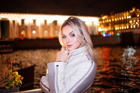 Stylish and elegant young woman in a beige coat on the city waterfront. Night city in autumn. Portrait of charming blonde at night outdoors, city lights at night. Stock Photo