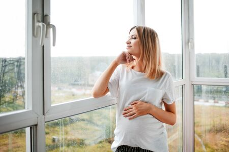 Portrait of a pregnant happy woman standing at the panoramic window on a fresh rainy autumn day, smiling at her thoughts, stroking her tummy. Blurred background. 免版税图像