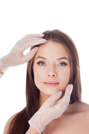 Cosmetology and aesthetic surgery. Portrait of a young attractive woman, clean skin. Gloved hands touching face, isolated on white