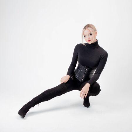 Strenge und junge Blondine in schwarzen kniehohen Stiefeln und schwarzer Kleidung. weißer Hintergrund