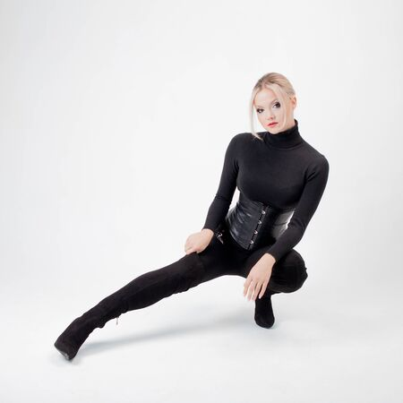 Strict and young blonde in black knee-high boots and black clothes. White background