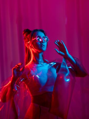 Stylish young woman in futuristic look, pink glowing background. Cyberpunk style, a girl in augmented reality glasses and wireless headphones listening to music, concept of future life technologies