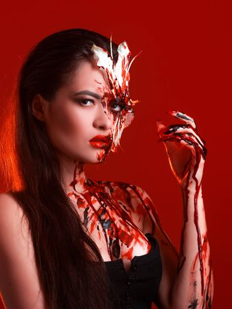 Blood Lily, scary and sexy Halloween look. Beautiful young brunette girl on red background. Blood flower, makeup face art