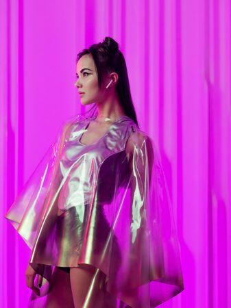 Cyberpunk e neon, una giovane ragazza di tendenza con un impermeabile in lattice trasparente. Stile futuristico al neon. Elegante giovane donna in look futuristico, sfondo rosa incandescente