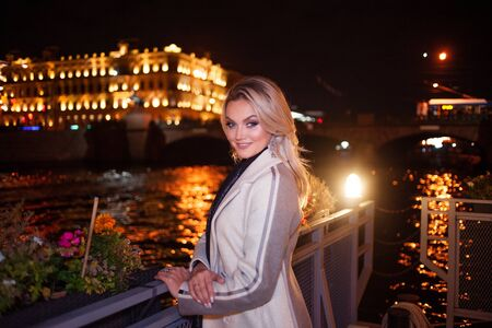 Stylish and elegant young woman in a beige coat on the city waterfront. Night city in autumn. 스톡 콘텐츠
