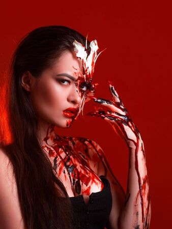 Blood Lily, scary and sexy Halloween image. Beautiful young woman with a bloody flower, make-up and makeup. 스톡 콘텐츠