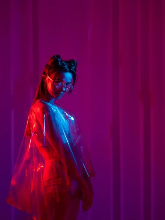 Cyberpunk and neon, a young trend girl in a transparent latex raincoat. Futuristic neon style, bright red backlight. Stylish young woman with glasses and hairdo in Asian anime style 스톡 콘텐츠