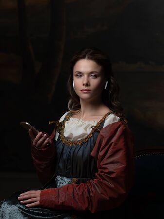 Stary i nowy, koncepcja. Piękna młoda kobieta w stylu renesansowym biorąc selfie na telefon. Piękna tajemnicza dziewczyna w stylu malarstwa renesansowego.