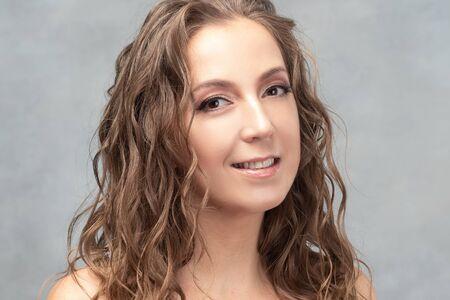 Retrato de una bella mujer joven con rizos mojados. Primer plano sobre un fondo claro.
