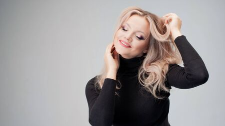 Charming blonde in a black turtleneck with sloppy curls, close-up portrait