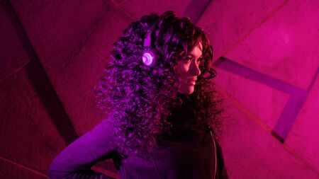 Young beautiful curly woman in big headphones listens to music, sings along, dances against the background of a wall, neon color, magenta. 스톡 콘텐츠