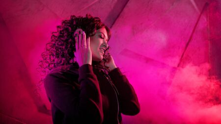 Young beautiful curly woman in big headphones smiles, listens to music, sings along, dances, jumps, closing her eyes, against the background of a wall, neon color, magenta.