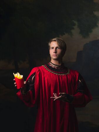 handsome man in a Royal red doublet eating fast food. funny duet of medieval style and modern attributes, concept. Stock Photo