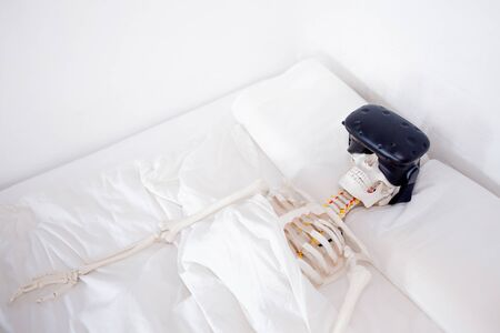 Gamer became interested in a computer game and died. A human skeleton in a VR helmet, lying in a white room on a bed. Standard-Bild