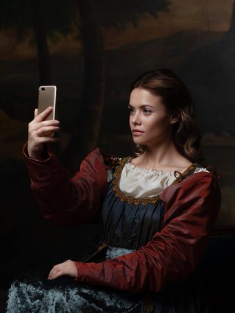 Old and new, concept. Beautiful young Renaissance style woman taking selfie on phone. Beautiful mysterious girl in the style of a Renaissance painting.