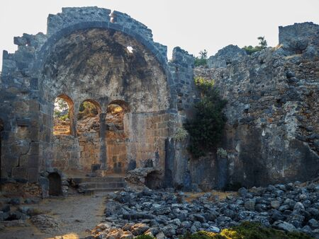 Ruins of the ancient city, ancient architecture. Walls and arches of an old ruined building, stones on the ground