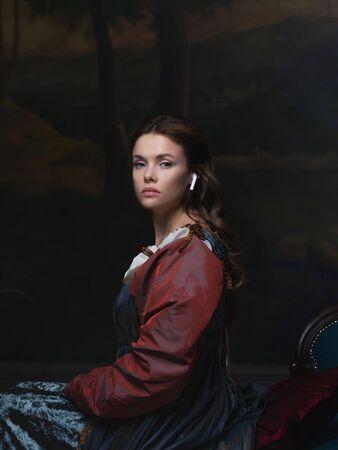 Stary i nowy, koncepcja. Portret dziewczynki z bezprzewodową słuchawką. Piękna młoda kobieta w stylu renesansowym