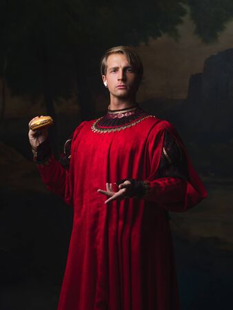 handsome man in a Royal red doublet eating fast food. funny duet of medieval style and modern attributes, concept.