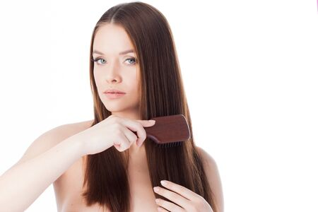 Attractive girl with long hair. Portrait of a beautiful young woman using a comb. White background