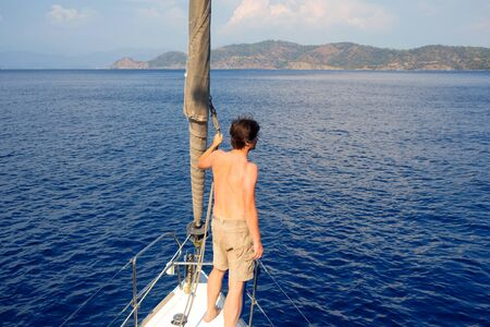 man in shorts stands on the deck near the sail, sailing and yachting, concept. Guy on a yacht trip on the background of the sea Archivio Fotografico - 134837388