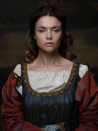 Portrait of a young woman in the style of a Renaissance painting. Beautiful mysterious girl in medieval dress Banco de Imagens