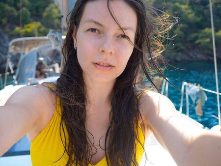 Selfie portrait of a positive multi-ethnic girl in a yellow swimsuit on Board a yacht. Boat trip Archivio Fotografico - 134837861