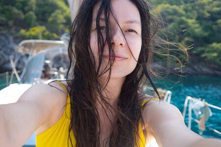 Selfie portrait of a positive multi-ethnic girl in a yellow swimsuit on Board a yacht. Boat trip Archivio Fotografico - 134837906
