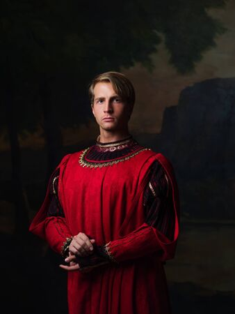 handsome man in a Royal red doublet. Young man, portrait in Renaissance style paintings Reklamní fotografie