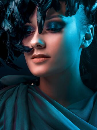 Luxurious mystical portrait, femme fatale in green. Portrait of a beautiful young girl with Smokey eye makeup