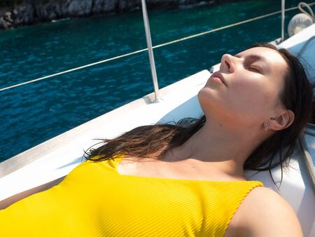young woman in a bright yellow one-piece swimsuit sunbathing on the deck of a sailing yacht. Holidays at the seaside, sunburn and sun protection Archivio Fotografico - 134837914