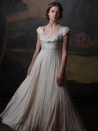 Beautiful young woman in a white long dress in the style of the 19th century. Portrait in the style of classical paintings Stock Photo
