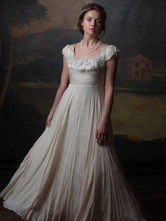 Hermosa mujer joven con un vestido largo blanco al estilo del siglo XIX. Retrato al estilo de las pinturas clásicas. Foto de archivo