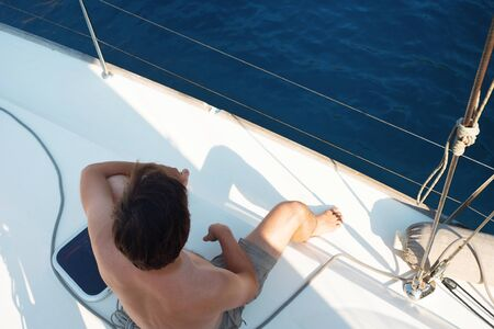 Rest on the sea, boat trip on a yacht. A young man in shorts sits on the deck and looks at the sea, sunbathing Archivio Fotografico - 134837968