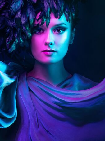 Luxurious mystical portrait, femme fatale in neon light. Portrait of a beautiful young girl with Smokey eye makeup and a hat of luxurious black feathers 版權商用圖片