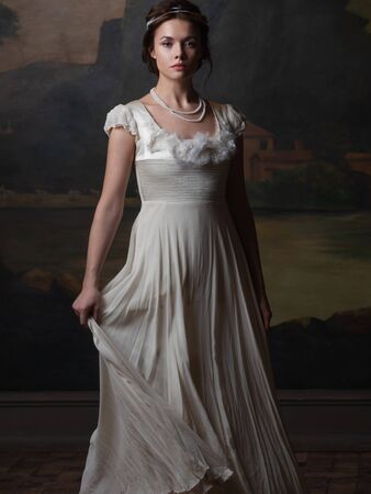 Beautiful young woman in a white long dress in the style of the 19th century. Portrait in the style of classical paintings