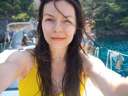 Selfie portrait of a positive multi-ethnic girl in a yellow swimsuit on Board a yacht. Boat trip Archivio Fotografico - 134838011