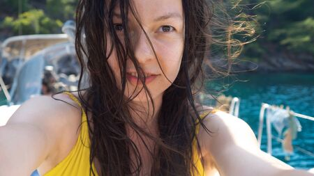 Vacation at the sea, young woman with wet hair after swimming, close-up portrait. Yacht trip